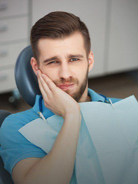 Man in dental chair holding jaw