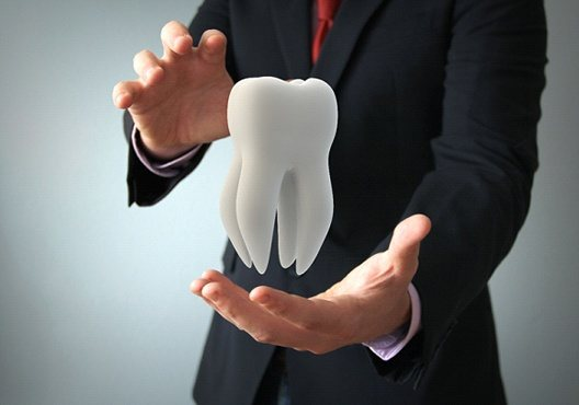 Man in suit holding a model for full mouth reconstruction
