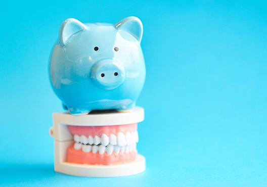 Blue piggy bank sitting on top of tooth model