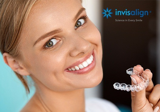 Smiling woman holding Invsialign tray