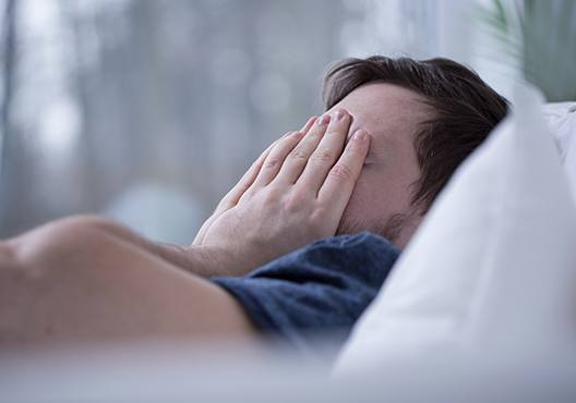 Frustrated man with hands over face in bed