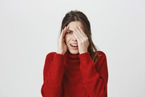 Woman wearing a red sweater is covering half of her face with her hand and shielding the other half with her other hand in embarrassment